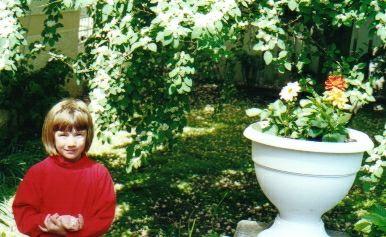Emma ställde sig bredvid en blompotta